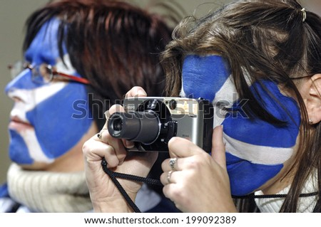 SAINT ETIENNE, FRANCE-SEPTEMBER 30, 2007: scottish fans girls with national flag masked face, taking picture during the Rugby World Cup match Italy vs Scotland, in Saint Etienne. - stock photo