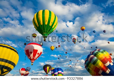 SAINT-JEAN-SUR-RICHELIEU, QUEBEC, CANADA - AUG. 16: Dozens of colorful hot air balloons take flight at the International Hot Air Balloon Festival of Saint-Jean-sur-Richelieu on August 16, 2011 in Saint-Jean-sur-Richelieu, Quebec, Canada. - stock photo