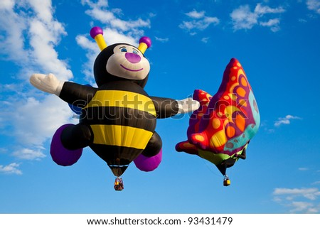 SAINT-JEAN-SUR-RICHELIEU, QUEBEC, CANADA - AUG. 16: Hot air balloons called Baby Bee and Betty Jean the Butterfly take flight at the International Hot Air Balloon Festival of Saint-Jean-sur-Richelieu - stock photo
