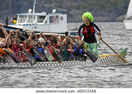 SAINT JOHN, CANADA - AUGUST 28: A sweep in a green wig steers his boat at the Saint John Dragon Boat Festival on August 28, 2010 in Saint John, Canada.
