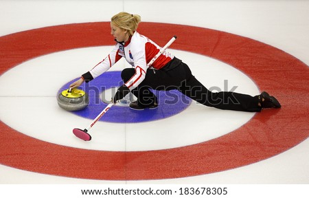 SAINT JOHN, CANADA - March 19: Christine Svensen of Denmark slides through the rings on her stone delivery at the Ford World Women's Curling Championship March 19, 2014 in Saint John, Canada. - stock photo