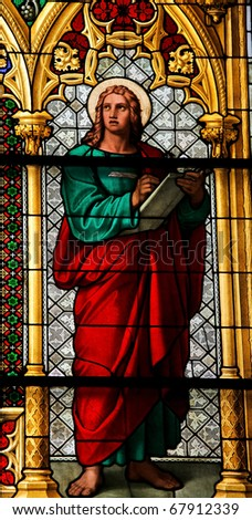 Saint John the Evangelist - author of the Apocalypse, stained glass church window in the Dom of Cologne - stock photo