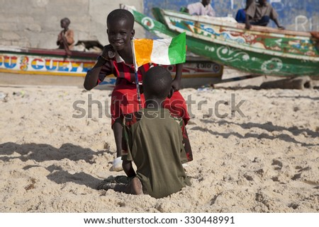 SAINT LOUIS, SENEGAL, DECEMBER 17: Two Kids playing on the beach, one is smiling and the other one is carrying a Senegalese flag, Senegal, December 17, 2013 - stock photo