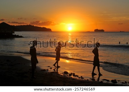 SAINT LUCIA, CARIBBEAN - DECEMBER 10, 2014:  Silhouettes of people admiring the sunset and cruise ship in the background
