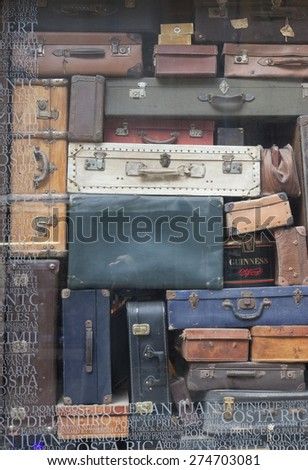SAINT-MALO, FRANCE - JULY 6, 2011: Ancient suitcases in window display in Saint-Malo, France. On the glass is text with a lot of travel destinations. The town is a main tourist attraction. - stock photo