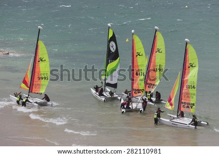 SAINT-MALO, FRANCE - JULY 6, 2011: Group of teenagers learning catamaran sailing on the coast of Saint-Malo. Their Hobie Cat 15 catamarans are 15 feet long and have a great buoyancy. - stock photo