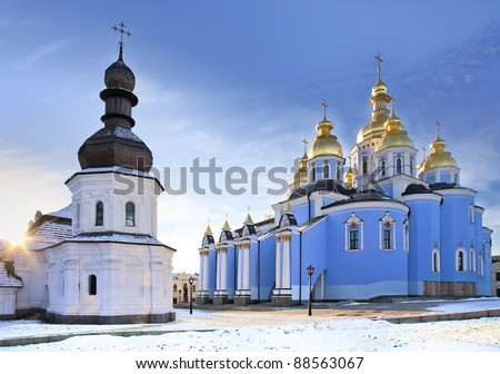 Saint Michael Gilded Russian Orthodox cathedral and a church with wooden dome in snow, Kiev, Ukraine - stock photo