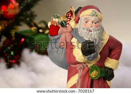 Saint Nick figurine with bag of presents and hint of lit Christmas tree behind him.