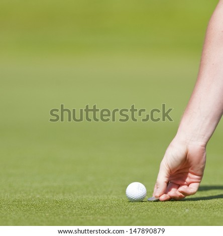 SAINT-OMER, FRANCE. 17-06-2010, A golfer marks his position on a green during the European Tour, 14th Open de Saint-Omer, part of the Race to Dubai tournament and played at the AA Saint-Omer Golf Club - stock photo