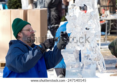 SAINT PAUL, MN/USA  JANUARY 25, 2015: Ice sculptor creates piece for competition at Saint Paul Winter Carnival. It is the nation's oldest winter festival attracting over 250,000 visitors a year. - stock photo