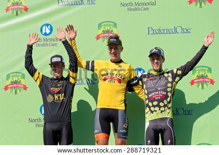 SAINT PAUL, MN/USA - JUNE 17, 2015: Tom Zirbel (center) wins Stage One as Ben Hill (left) and Michael Sheehan (right) take second and third, respectively at pro cycling time trial in Saint Paul.  - stock photo