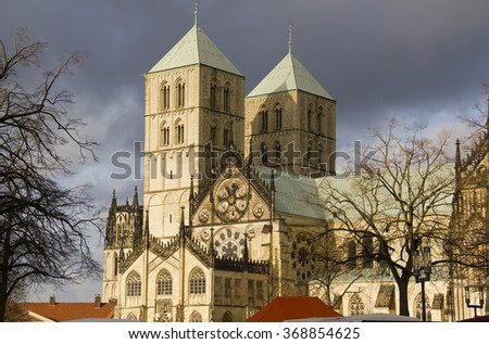 Saint Paulus Cathedral in Munster, Germany, in winter sunlight with dark rainclouds  - stock photo