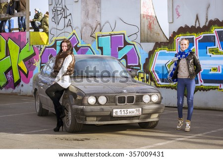 SAINT-PETERSBURG, RUSSIA - APRIL 5, 2014: Beautiful young girl posing about old-car BMW 5-series e34 at the meeting fans of the Bavarian automaker, St. Petersburg, Russia - stock photo