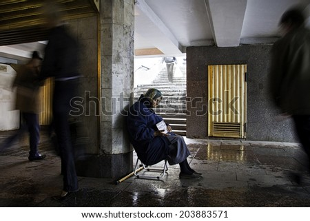 SAINT PETERSBURG, RUSSIA - AUGUST 8: A beggar woman sitting on a rainy day in an underground passage passing the 4.5 km long street in the historic center on August 8, 2008 of St. Petersburg, Russia.