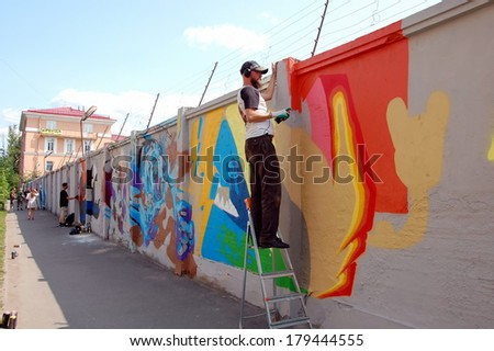 SAINT-PETERSBURG, RUSSIA, JULY 9,  2013: Graffiti artists  draw  a picture on the wall in St-Petersburg