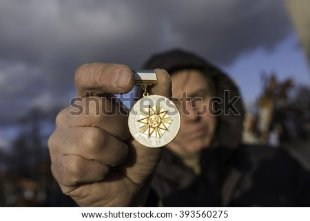 Saint-Petersburg, Russia - March 18, 2016: the rally on the occasion of the second anniversary of the reunion of Crimea to Russia, Man shows a commemorative medal in honor of the liberation of Crimea  - stock photo