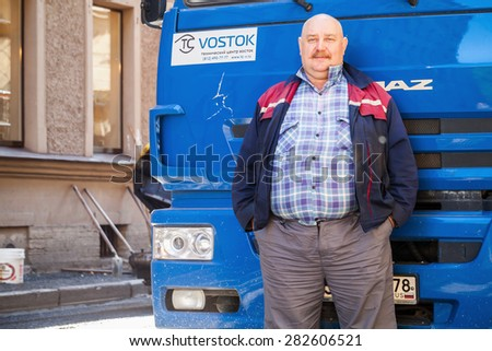 Saint-Petersburg, Russia - May 30, 2015: Senior positive truck driver with mustaches stands near his blue Kamaz lorry cabin - stock photo