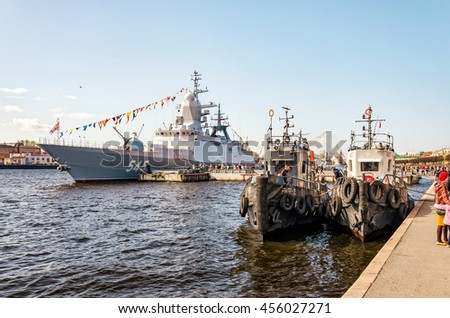 Saint Petersburg, Russia, May 9, 2015. Victory Day celebration. Two tugboats and a warship moored at the Lieutenant Schmidt embankment.