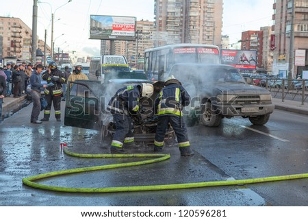 SAINT-PETERSBURG, RUSSIA-NOVEMBER 11: Firefighters and owner are near burned car on city street on November 11, 2012 in Saint-Petersburg, Russia. Self-ignition car wiring. No one was injured.