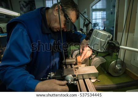 Saint-Petersburg, Russia - November 10, 2016: Machine shop for the production of gears and other small parts for mechanical watches. Specialist watchmaker at work.