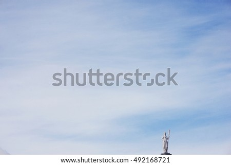 SAINT PETERSBURG, RUSSIA. Petropavlovskaya fortress. Sculpture allegory navigation - statue of a woman with the paddle on the rooftop Botnia house on a background of blue sky.