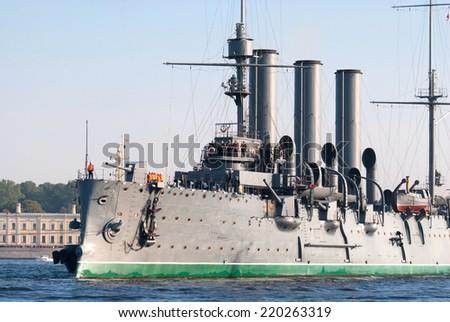 "SAINT-PETERSBURG, RUSSIA, September 21: Towing cruiser ""Aurora"" on the river Neva, 21 September 2014 in St-Petersbur. Legendary cruiser ""Aurora"" goes  to overhaul the docks of the island of Kronstadt. - stock photo"