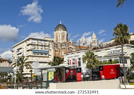 SAINT RAPHAEL, FRANCE - SEPTEMBER 12, 2014: Casino in the Mediterranean Coast village of Saint-Raphael. Behind, the dome and the bell towers of the Basilica of Our Lady of Victory of Lepanto - stock photo