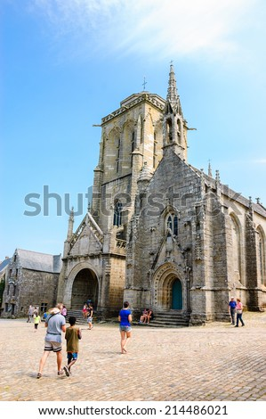 Saint Ronan church in  medieval village Locronan and tourists at the square in front of it. Brittany, France. - stock photo