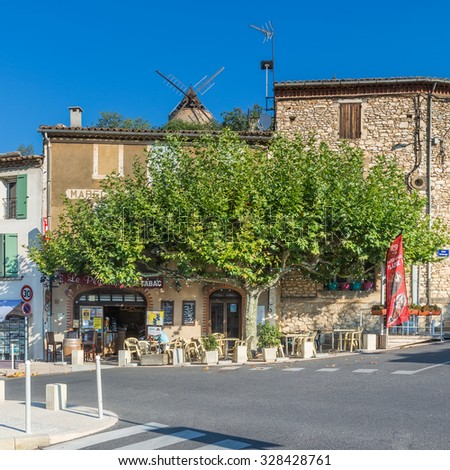 SAINT-SATURNIN-LES-APT, FRANCE - AUGUST 11, 2015: City centre with cafe bars and restaurants and people sitting under the tree at local Cafe with windmill in the background.