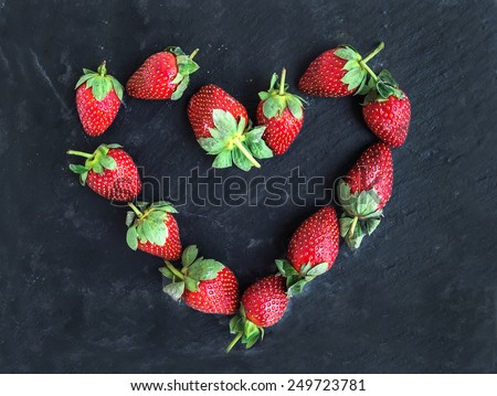 Saint Valentine's day greeting berry set: fresh garden strawberries placed together in a shape of heart over a rough black stone background. Top view - stock photo