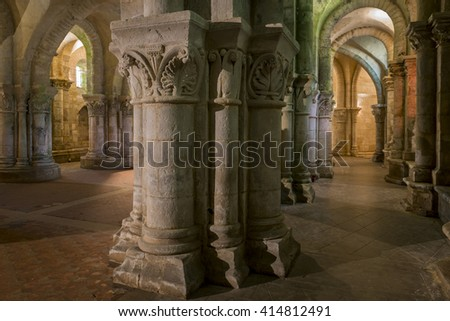 Saintes, France - August 22, 2014: Crypt of a church in Saintes France with many pillars and sunflowers.