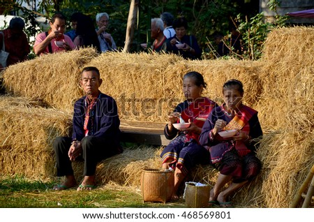 SAKON NAKHON, THAILAND - JANUARY 17 : Older Phu Tai people sit and eat breakfast at stack rice straw in morning time at Ban Non Hom on January 17, 2016 in Sakon Nakhon, Thailand