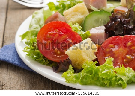 salad and fresh vegetables on wood background