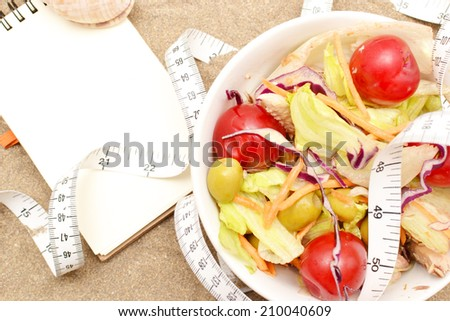Salad and tape measure on sand