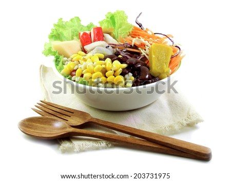 Salad and wood spoon, fork on cloth isolated on white background