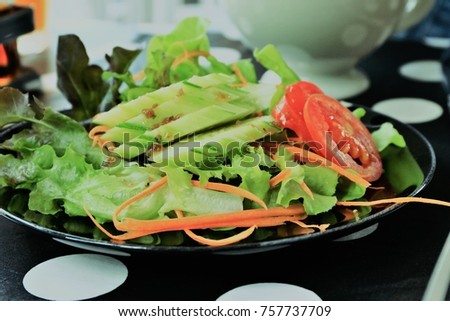 Salad bowl with green leaf and tomato and cucumber and carrot put on black dish on table