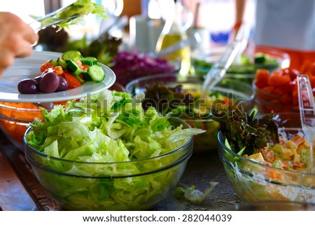 Salad buffet. The people themselves impose the desired treat. - stock photo