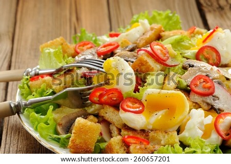 Salad Caesar with mushrooms, eggs, chili and radish with two forks on wooden background closeup
