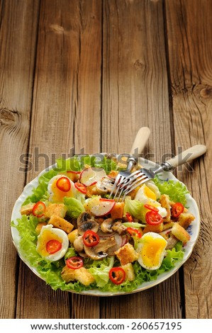 Salad Caesar with mushrooms, eggs, chili and radish with two forks on wooden background with space vertical - stock photo