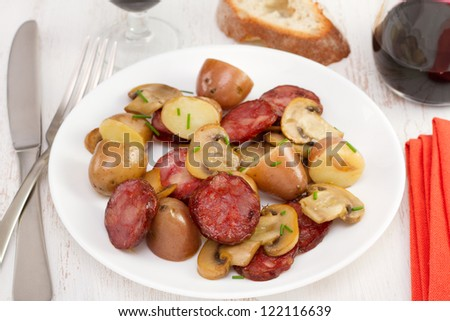 salad chorizo with potato and fried champignons on the plate