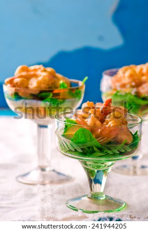 salad - cocktail with shrimps, avocado and arugula in glass vases. selective focus