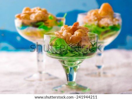 salad - cocktail with shrimps, avocado and arugula in glass vases. selective focus - stock photo