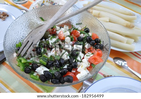 Salad consisting of olives, goat cheese, tomatoes, peppers, and herbs in front of a bowl of white asparagus  - stock photo