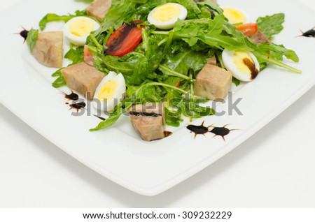 salad - egg halves, pork cubes, roquette and tomatoes - stock photo