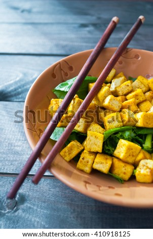 Salad from fried tofu with curry and fresh spinach in brown bowl with chopsticks. Asian cuisine - stock photo