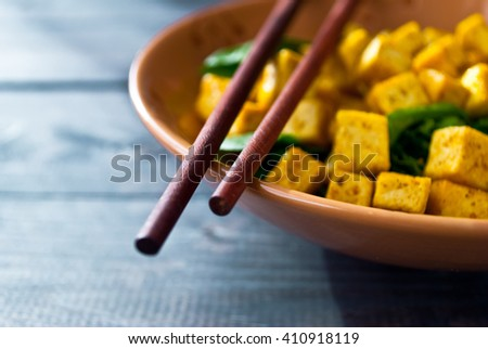 Salad from fried tofu with curry and fresh spinach in brown bowl with chopsticks. Selective focus - stock photo