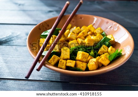 Salad from fried tofu with curry and fresh spinach in brown ceramic bowl with chopsticks - stock photo