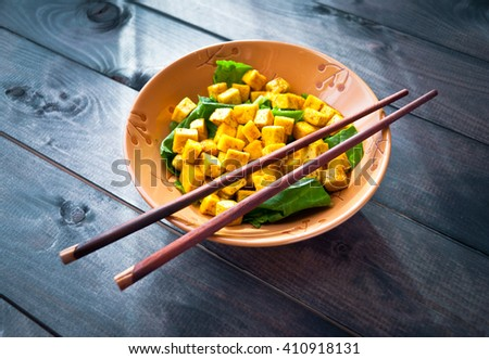 Salad from fried tofu with curry and fresh spinach served in brown bowl with chopsticks on grey wooden background - stock photo