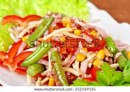 Salad from ham, tomato, green beans, corn and greens - stock photo