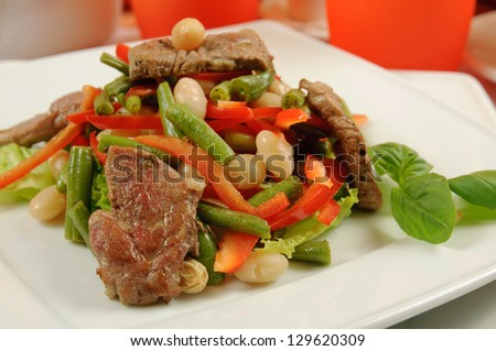Salad from roasted meat, beans, pepper, lettuce, basil and asparagus in a restaurant - stock photo